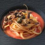 Spaghetti con fritto di Capperi, Bucce di Melanzana e Giarratana su acqua di Pomodoro al Basilico Alpino